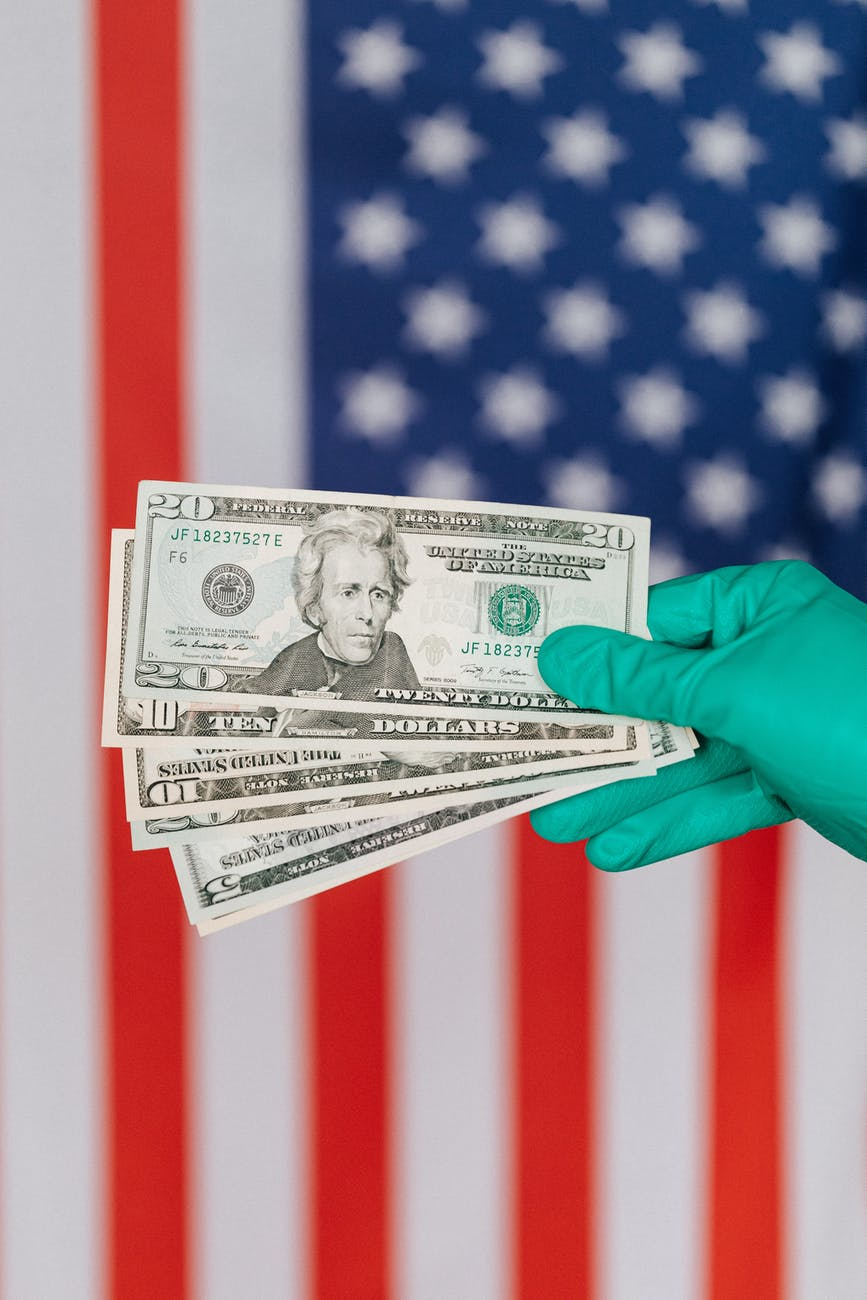 crop person showing various dollars near american flag